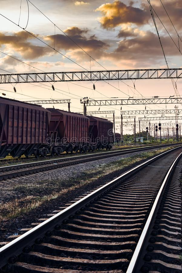 Railroad infrastructure during beautiful sunset and colorful sky, railcar for dry cargo, transportation and industrial concept royalty free stock photography