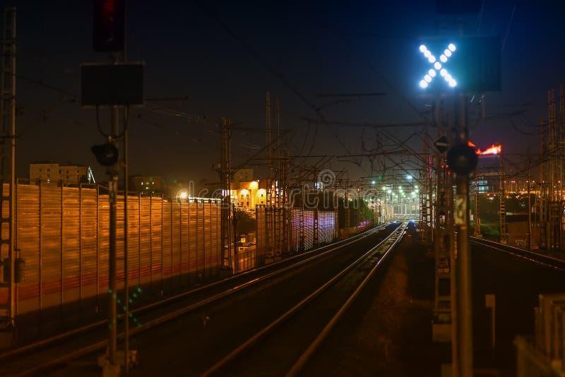 Railroad la scena di notte con le piste del semaforo blu e della stazione ferroviaria, al crepuscolo, i toni e colori dorati indu immagine stock