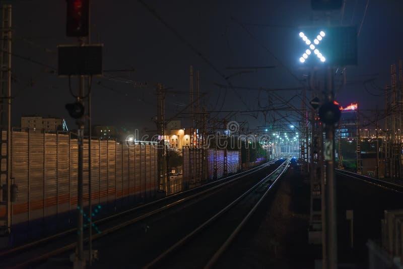 Railroad la scena di notte con le piste del semaforo blu e della stazione ferroviaria, al crepuscolo, i toni e colori freddi indu fotografia stock libera da diritti