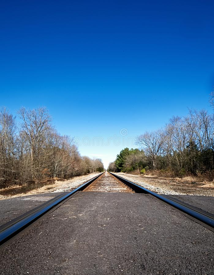A closeup of railroad tracks leading into infinity and a brilliant blue sky. royalty free stock photo