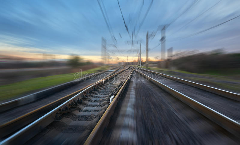 Railroad in motion at sunset. Railway station. With motion blur effect against blue sky, Industrial concept background. Railroad travel, railway tourism royalty free stock image