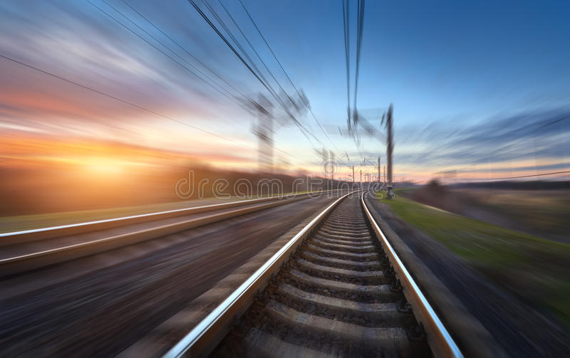 Railroad in motion at sunset. Railway station. With motion blur effect against colorful blue sky, Industrial concept background. Railroad travel, railway royalty free stock photo