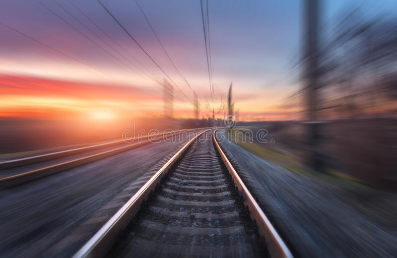 Railroad in motion at sunset. Railway station. With motion blur effect against colorful blue sky, Industrial concept background. Railroad travel, railway royalty free stock photography