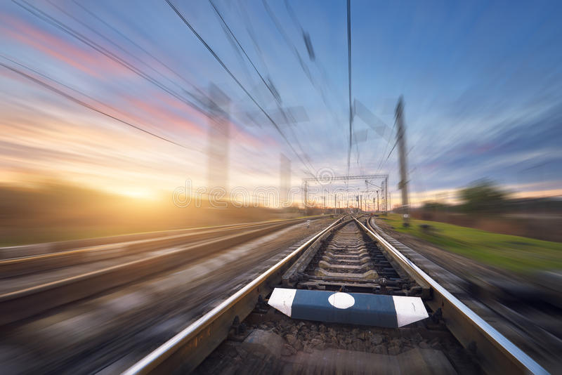 Railroad in motion at sunset. Railway station. With motion blur effect against colorful sky, Industrial concept background. Railroad travel, railway tourism stock image