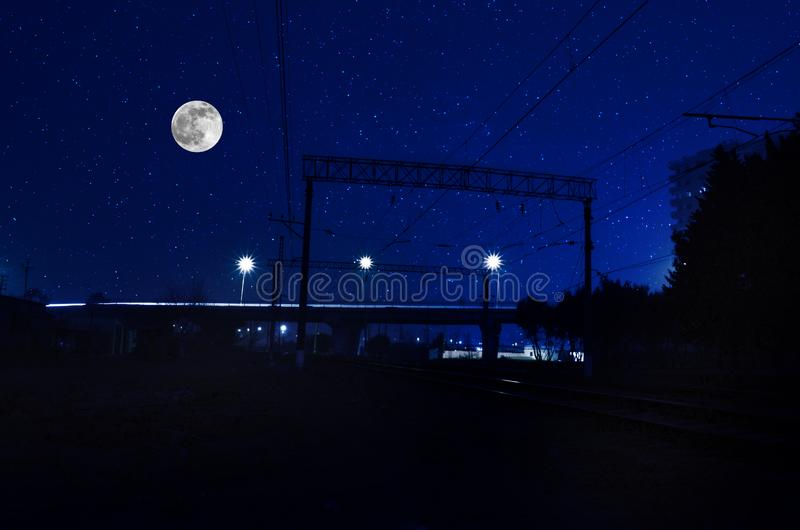 railroad in night under full moon. Beautiful night landscape with bridge over the railroad royalty free stock photo