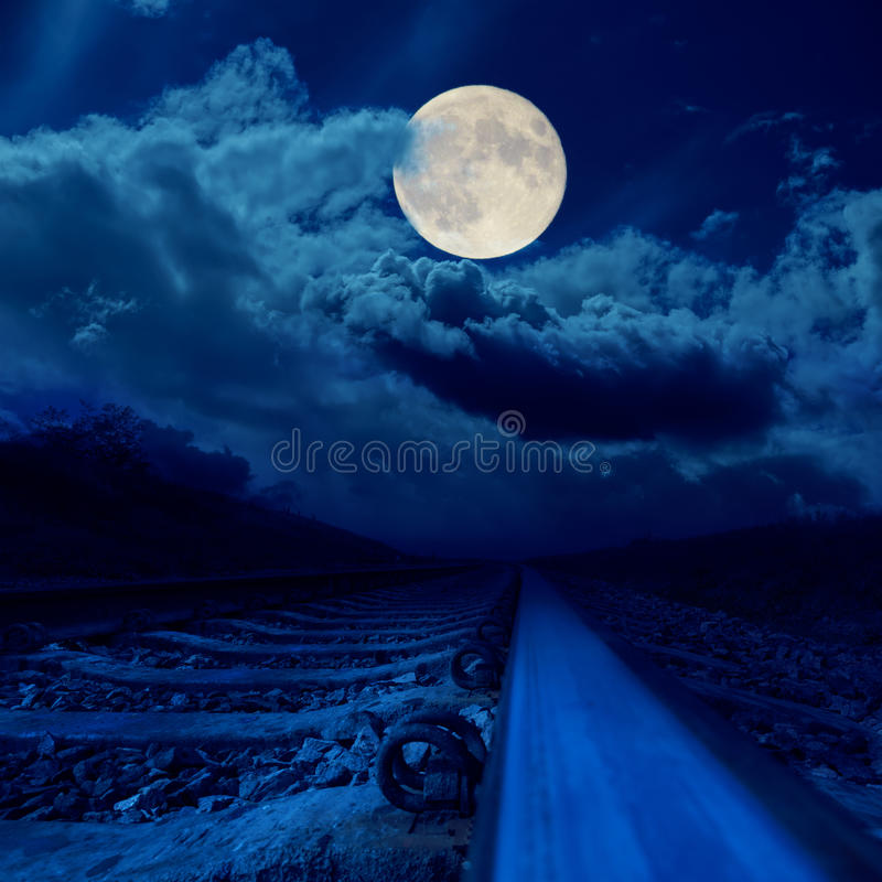 railroad in night under full moon in clouds royalty free stock image