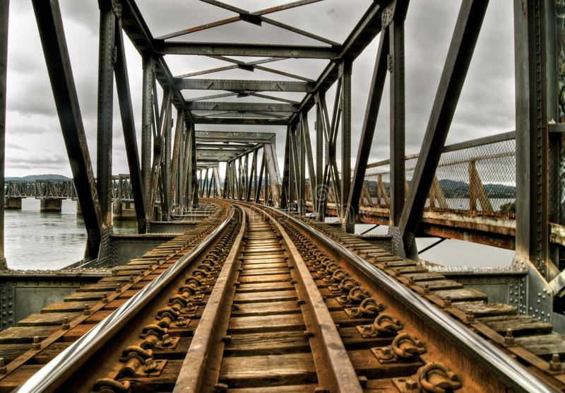 Railroad old rusty bridge crossing a lake in tauranga new zealand. Railroad old rusty bridge in tauranga new zealand royalty free stock image