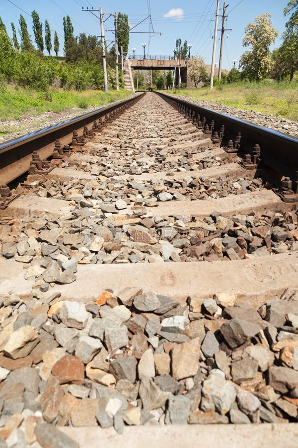 The railroad, rails for trains. VOLGOGRAD, RUSSIA - May 28, 2017: Railway rails and a way for trains against the background of the city bridge in are solar day stock photography