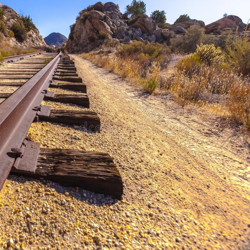 Railroad track in a dry and rocky desert royalty free stock images