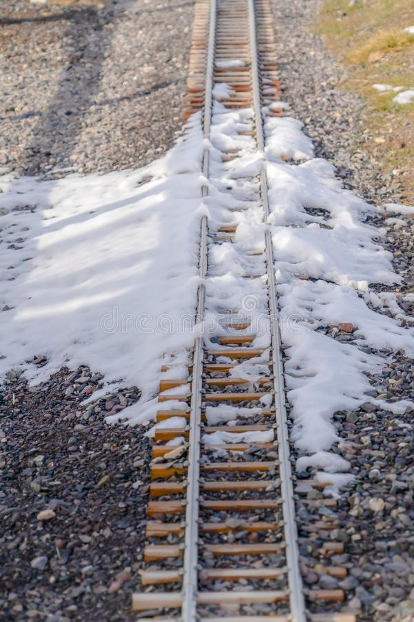 Railroad track with snow on a sunny winter day. Sunny day view of a railroad track along a rocky ground. Powdery white snow can be seen on the railway in royalty free stock photo