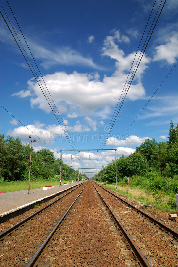 Railroad tracks. With power lines seemingly disappearing into infinity, against blue cloudy vibrant sky stock photography