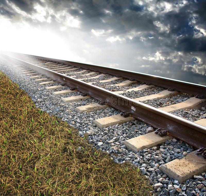 Railroad tracks. On a bed of rock on a grassy surface. Cloudy background with strong lighting to the left of the image. Concept for exploration or adventure royalty free stock photo
