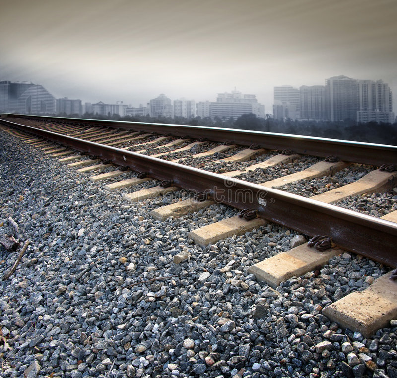 Railroad tracks. On a bed of rock with a city scape in the background. Urban concept royalty free stock photography