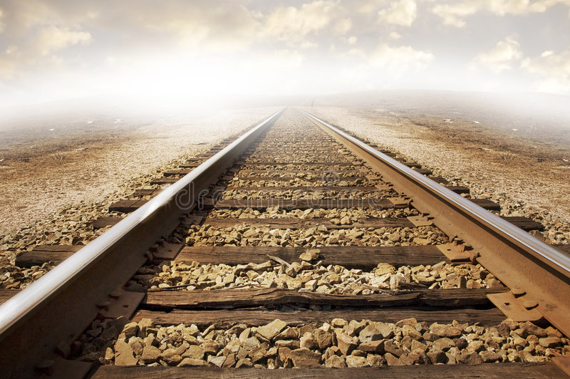 Railroad tracks. On a bed of rock stretching out across parched dry landscape. Cloudy background with strong lighting to the left of the image. Concept for royalty free stock photo