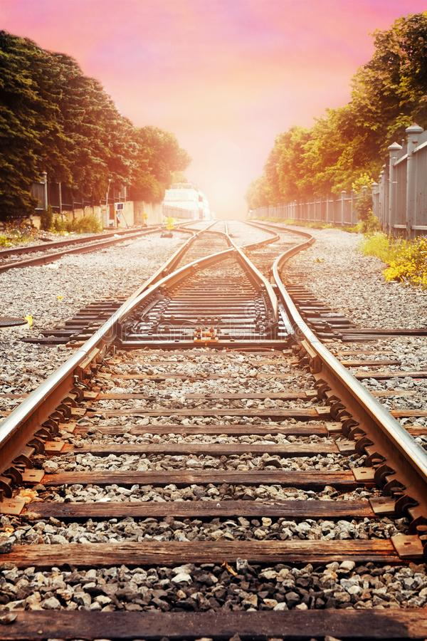 Railroad tracks against beautiful sky at sunset. Industrial landscape with railway, colorful pastel sky with clouds, sun and trees royalty free stock photo