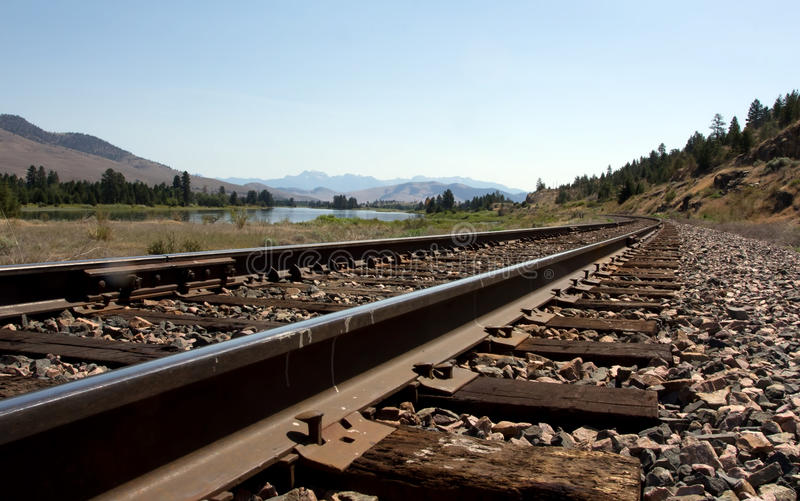 Railroad Tracks along the River. This image of the railroad tracks with the river, trees and mountains in the background was taken at ground level in NW Montana stock images