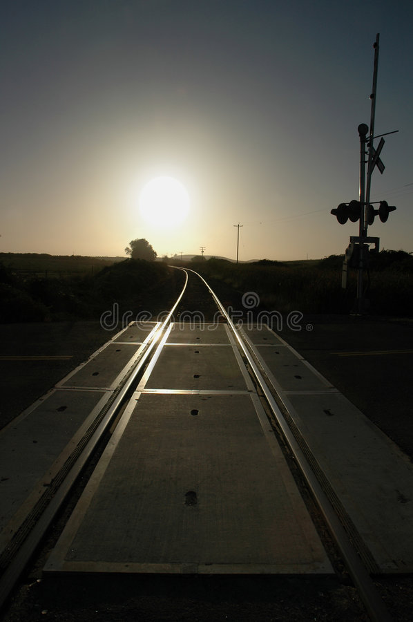 Railroad Tracks and Crossing. Brilliantly Backlit ByRising Sun royalty free stock images