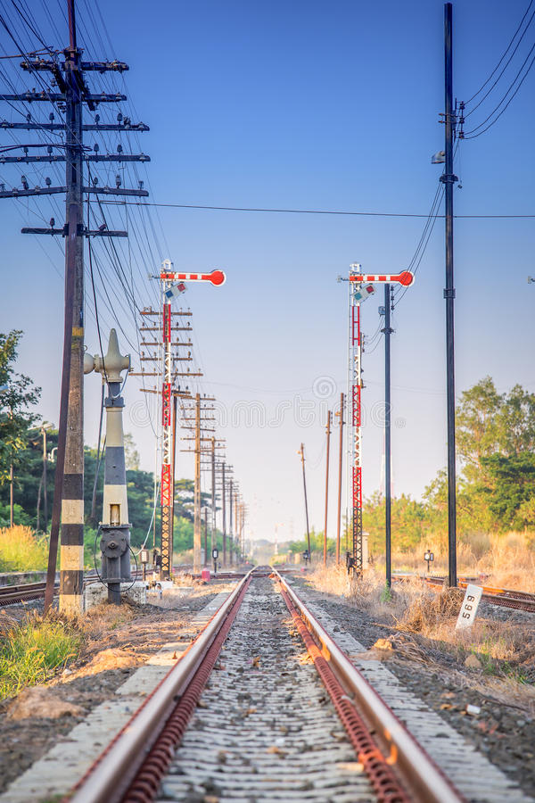 Railroad tracks disappear to the vertical under a bright blue sky stock image