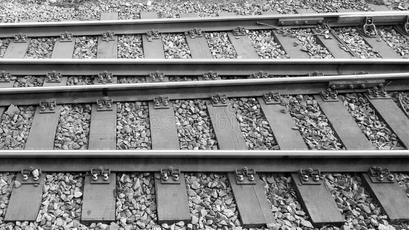 Train tracks in tandem. Railroad tracks diverge or converge from left to right. A black and white aerial view shows the metal rails and ties affixed to the royalty free stock photography