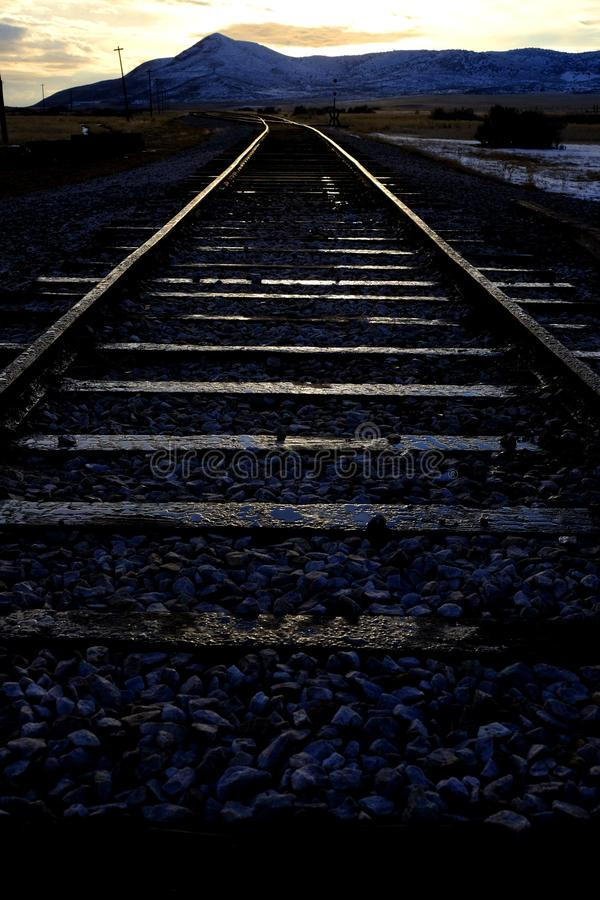 Railroad Tracks in Evening Warm Glow Reflection Traveling royalty free stock image
