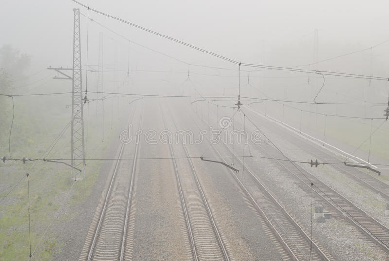 Railroad tracks in the fog. The outgoing rails are lost in thick fog stock image