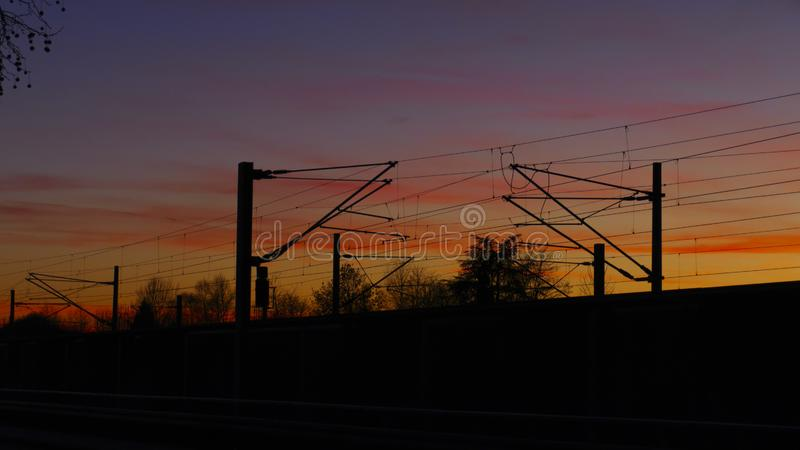 Railroad tracks, overhead lines, silhouette with trees, in  sunset. Railroad tracks, overhead lines, silhouette with trees, in the sunset, or in sundown stock photography