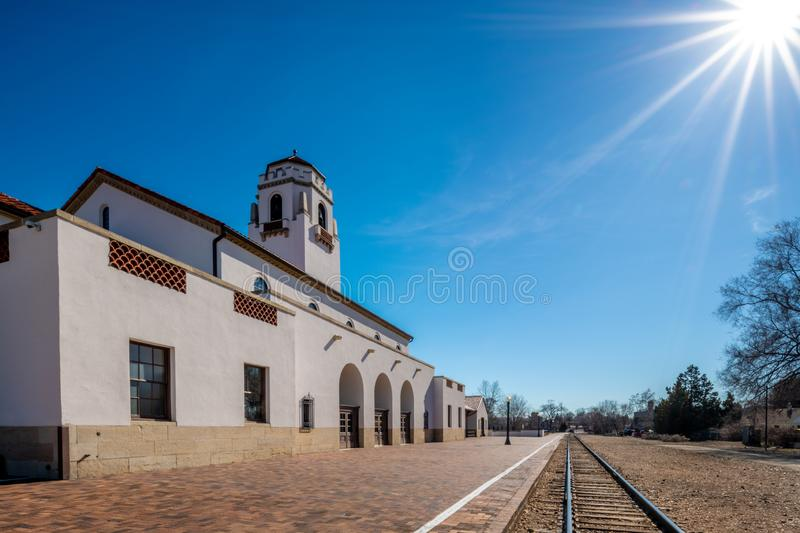 Railroad tracks pass by a local train depot with a huge sun star in the sky royalty free stock photography
