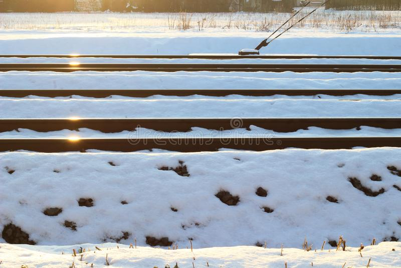 The railroad tracks rails in the snow on a sunny day. Transport, minimalism, reflection of rhe sun on railroad rails royalty free stock photos