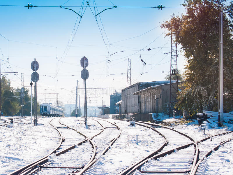 Railroad tracks running to the small snowbound station. Winter royalty free stock images