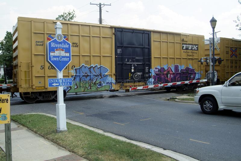 A railroad train boxcar with spray painted graffitti. A graffiti covered boxcar passes by railroad crossing in Riverdale Park, Maryland royalty free stock photo