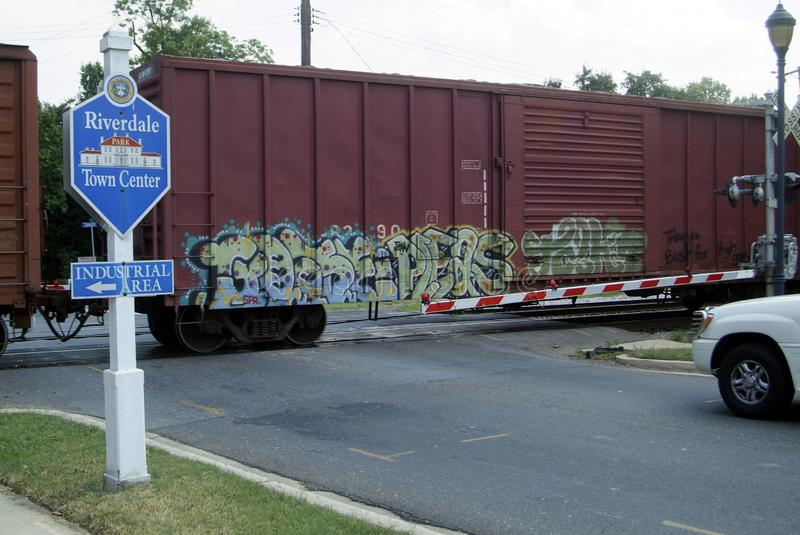 A railroad train boxcar with spray painted graffitti. Passes through a railroad crossing in Riverdale Park, Maryland stock photos