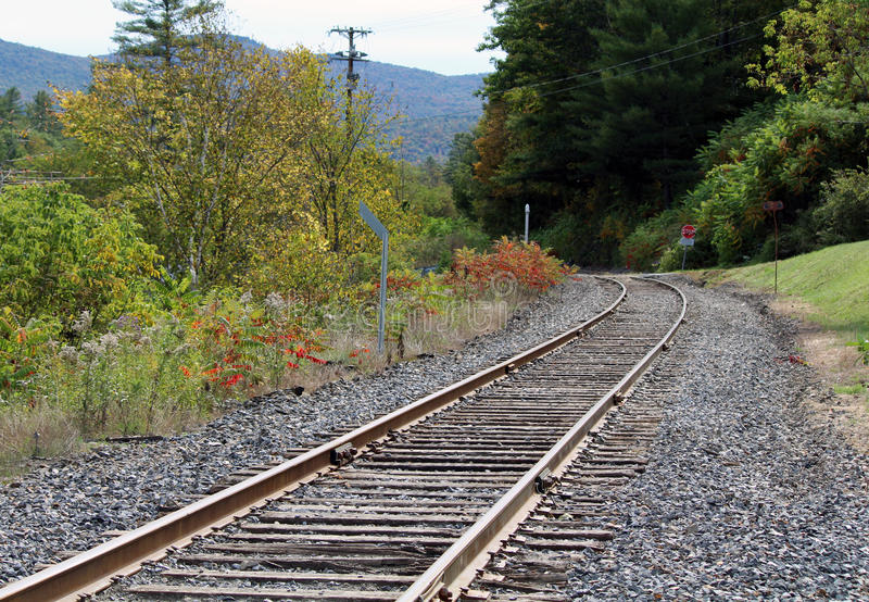 Railroad Train Tracks Going around a Corner. Railroad tracks with Autumn mountain scene. Winding around a corner. Stop sign and trees turning color in Vermont stock image
