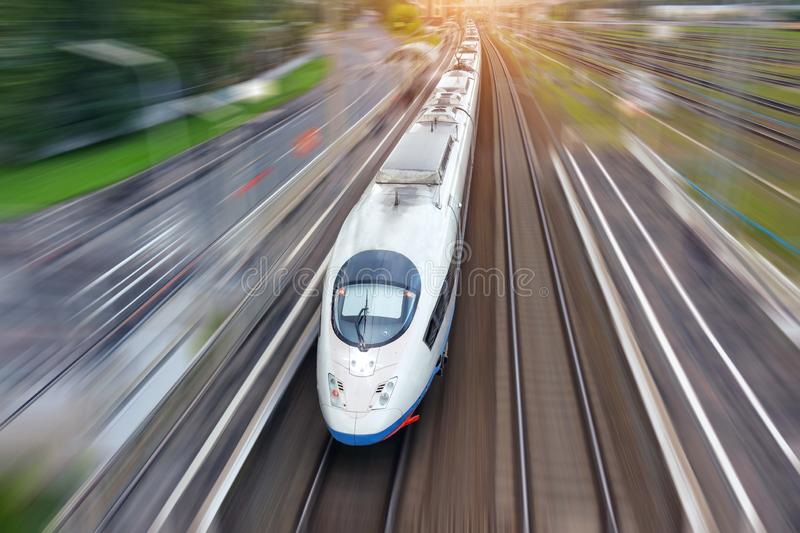Railroad travel high speed fast train passenger locomotive motion blur effect in the city, top aerial view from above.  royalty free stock image