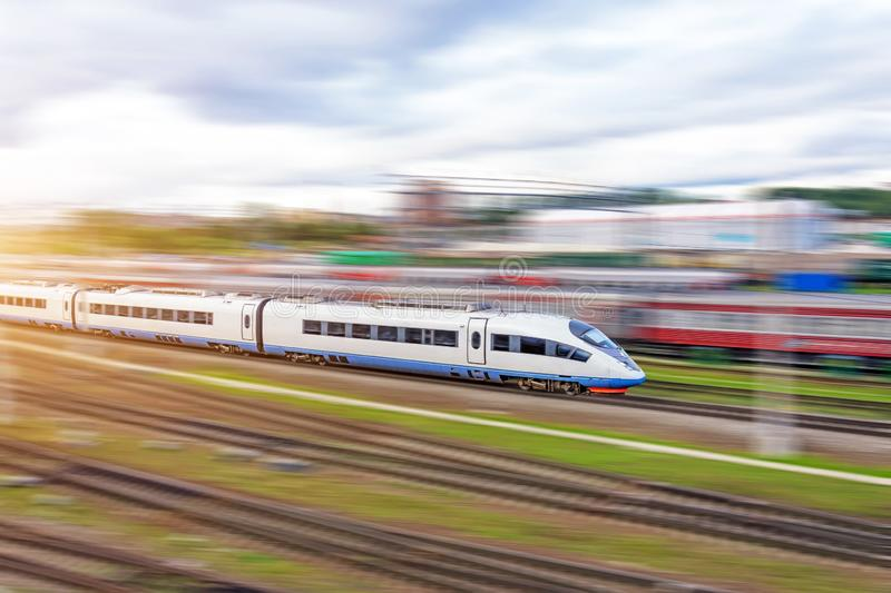 Railroad travel passenger train with motion blur effect, industrial a district of the city stock photo
