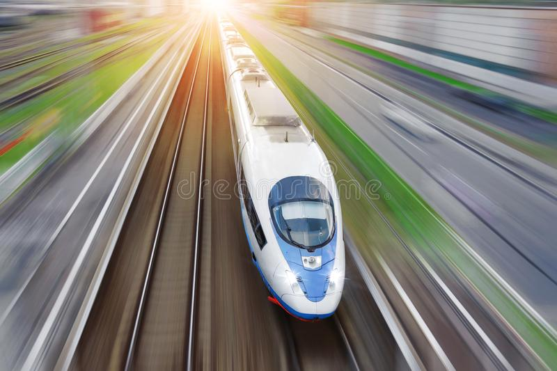 Railroad travel passenger train with motion blur effect, industrial a district of the city, top aerial view from above.  royalty free stock image
