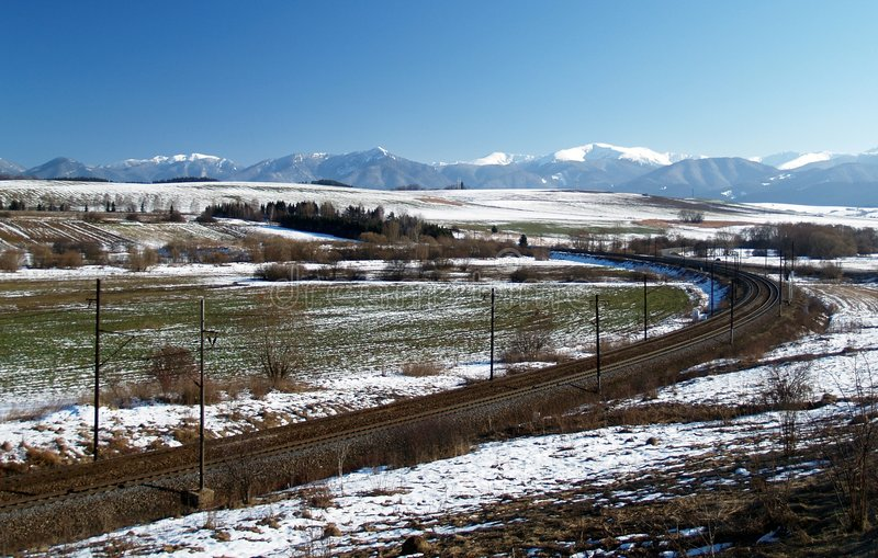 Railroad and winter prairie. Railroad or train tracks passing through open prairie with mountains in the background. Liptov region in Slovakia stock photos