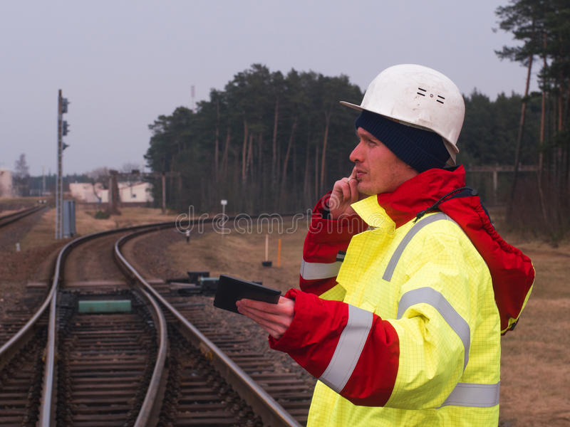 Railroad worker, Engineer in protective work wear and helmet talking by the phone. railroad tracks on the background.  royalty free stock photography