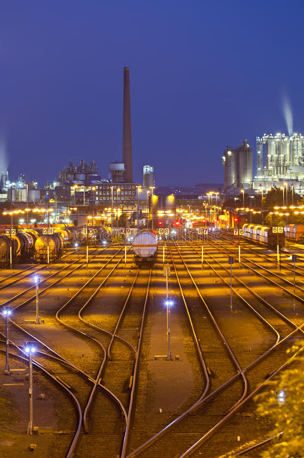 Railroad Yard And Industry At Night. An illuminated railroad yard with trains and other industry in the background at night stock photos