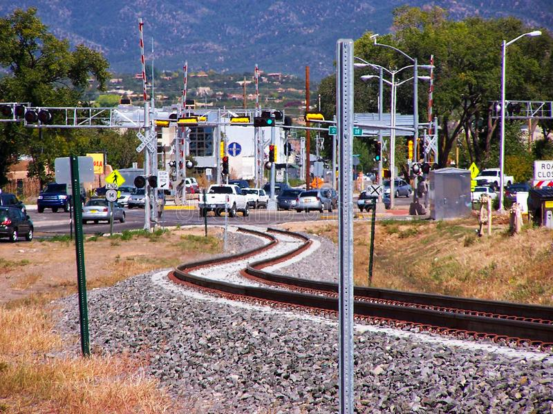 Curving railroad train tracks serpentine into one of the main traffic intersections in Santa Fe NM stock image