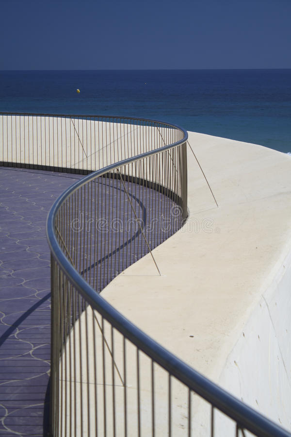 Rails and curves. A modern sea front promenade with curves and chrome rials royalty free stock photography