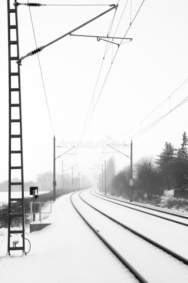 Rails dans la neige brumeuse image stock