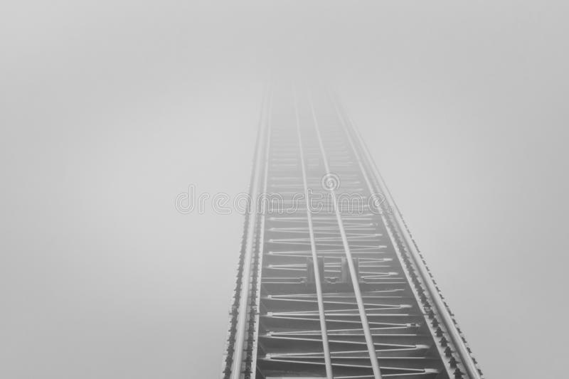 Rails that end in dense fog royalty free stock photo