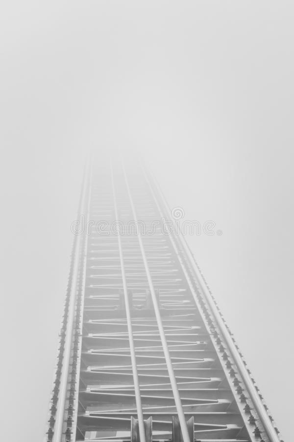 Rails that end in dense fog stock photo