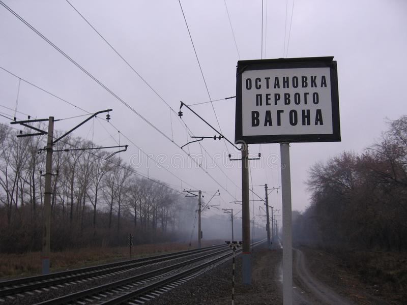 Rails ferroviaires dans le brouillard avec un arrêt de signe la première voiture à la station photo libre de droits
