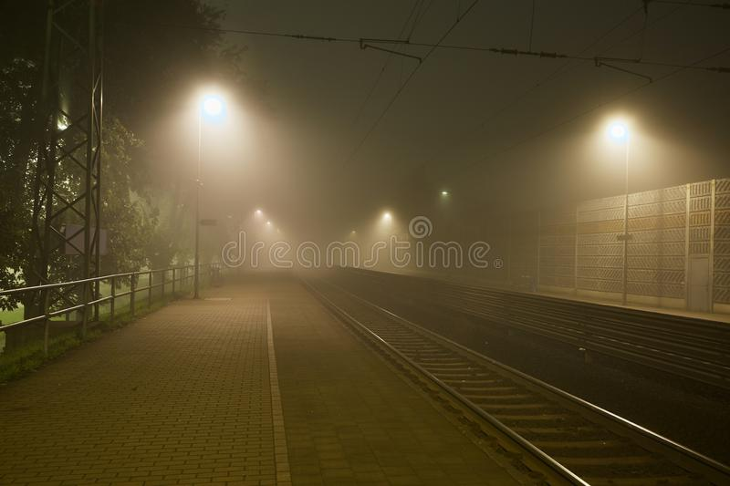 Rails in the fog. Railway station in the fog at night royalty free stock photo