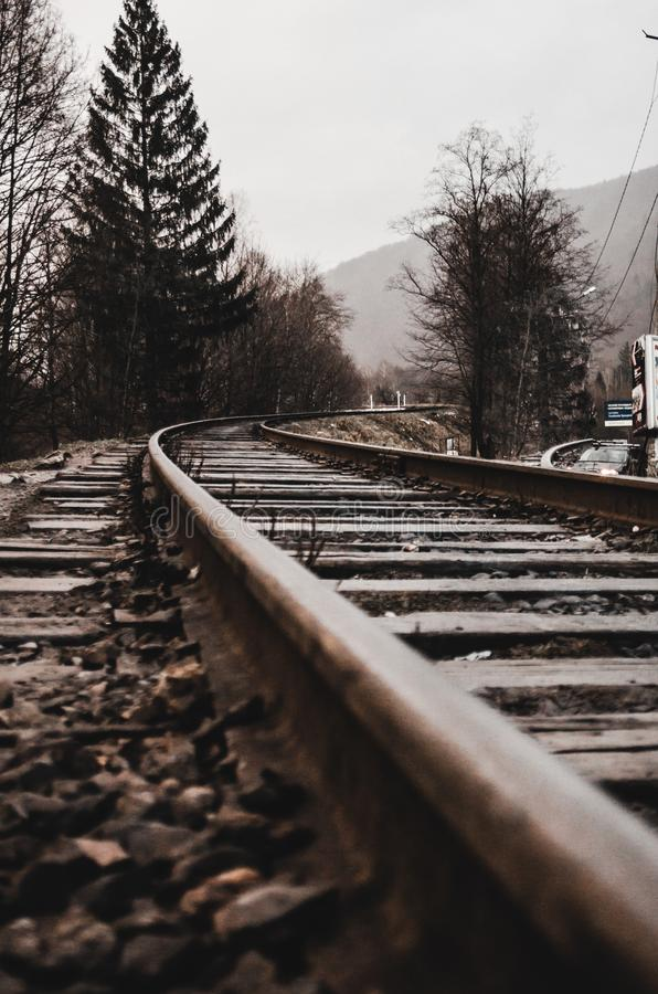Rails in foggy weather. In the morning concept. Trees and mountain are on the background. Empty railroad track going into the fog royalty free stock images