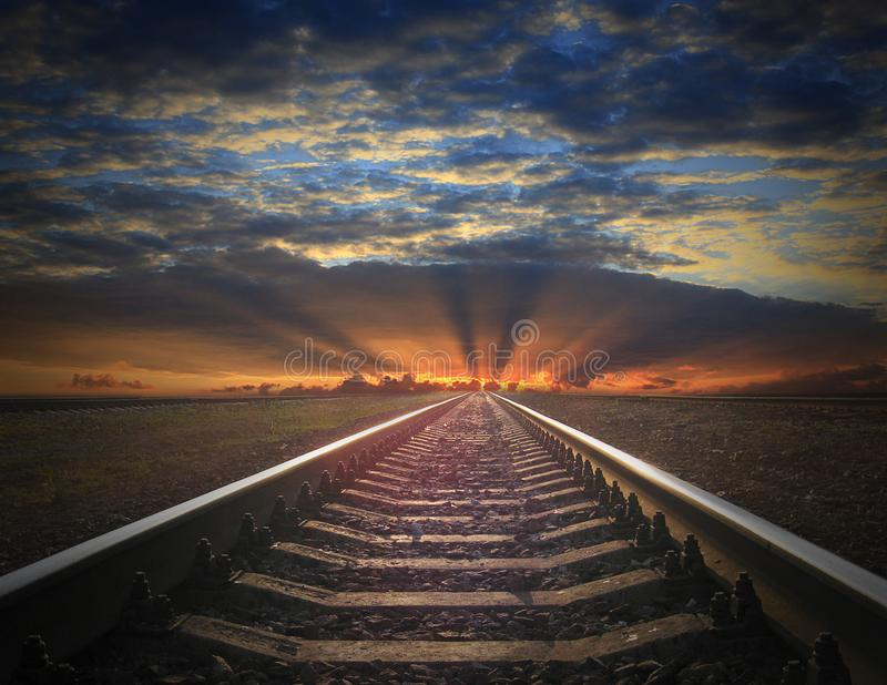 Rails going away into the fiery red sunset. View to the rails going away into the dark landscape with fiery red sunset royalty free stock photos