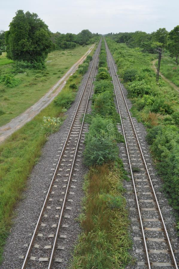 Rails and countryside. Rails going straight seen from a bridge. Thai countryside. Small dirt road follows the rails stock photos