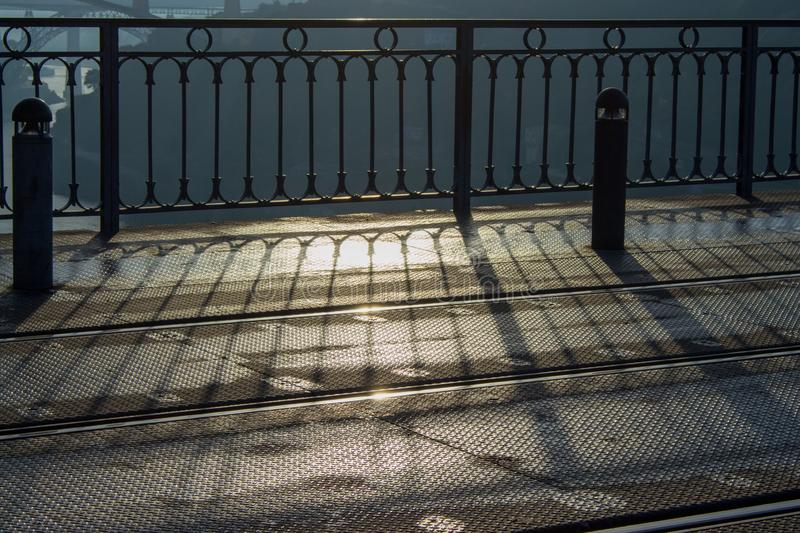 Rails and iron fence in morning light. Modern urban architecture. Shadow from metal fence early in the morning on the street. stock photography
