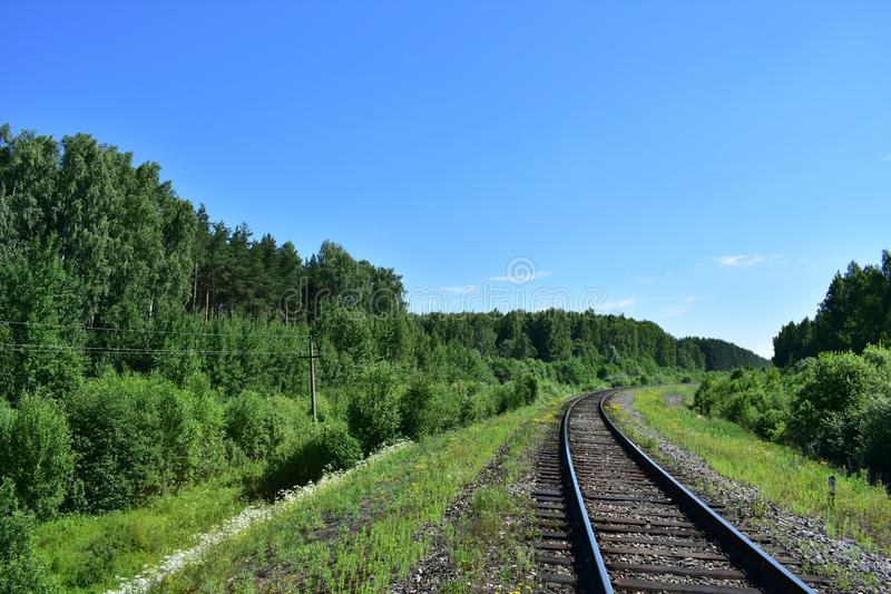 Rails the railway goes into the distance turn of a forest strip of grass sky royalty free stock image